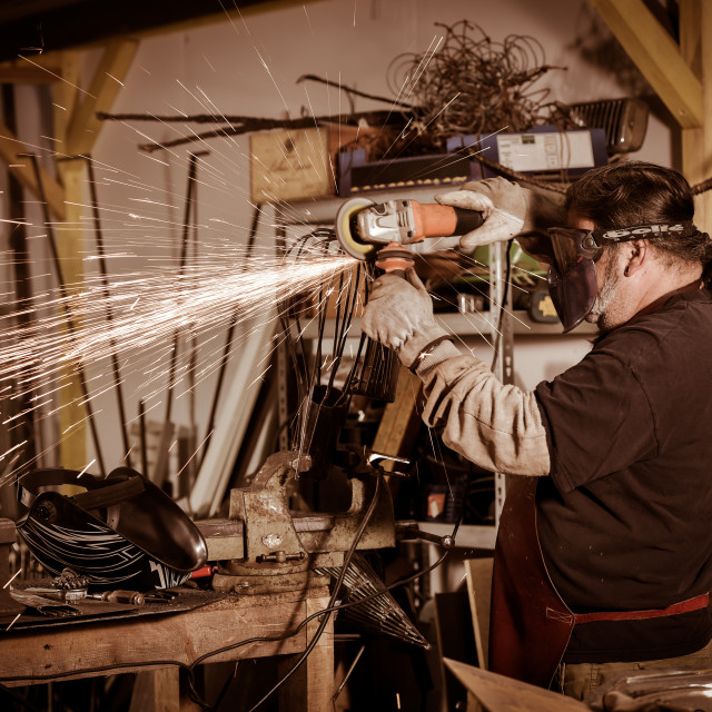 """Metal worker Grinding with sparks in workshop"" stock image"