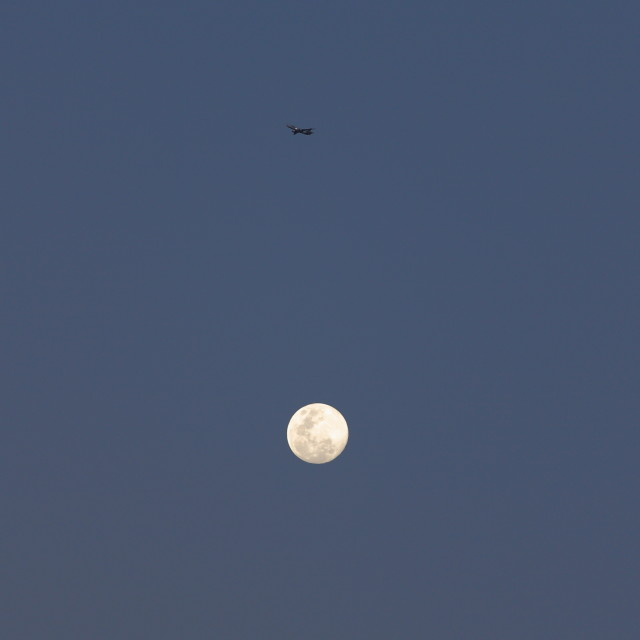 """Plane flies over the moon"" stock image"