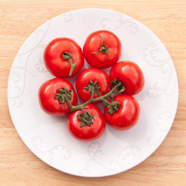 """Large beefsteak tomatoes on a white plate on a wooden background"" stock image"