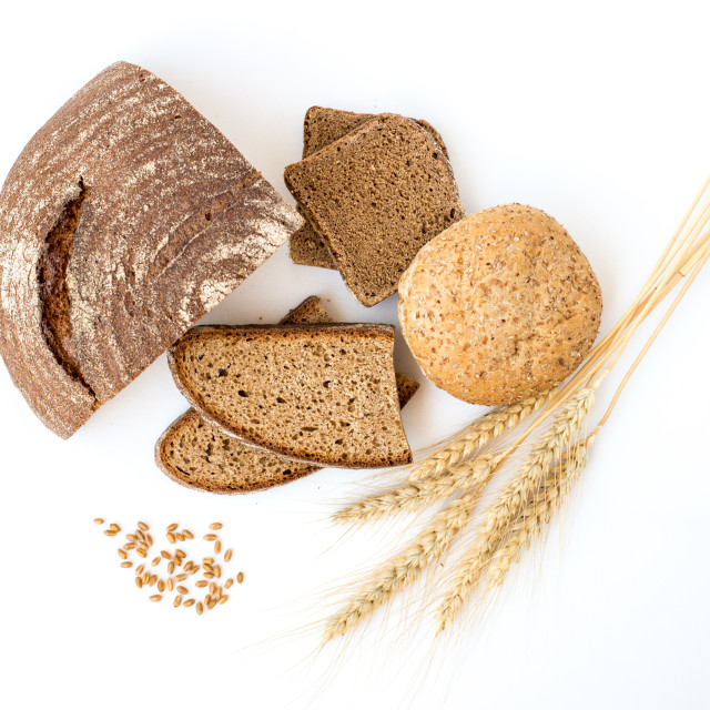"""Variety of bread and stalks of wheat isolated on white"" stock image"