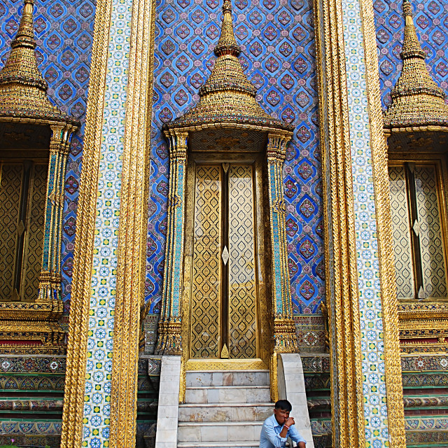 """Man on the steps of the Wat Phra Kaew, Bangkok, Thailand"" stock image"