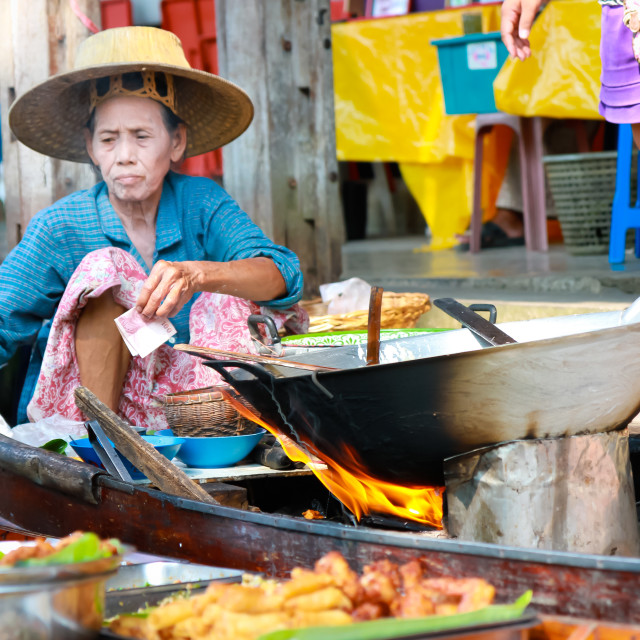 """Thai lady cooking with wok on boat"" stock image"