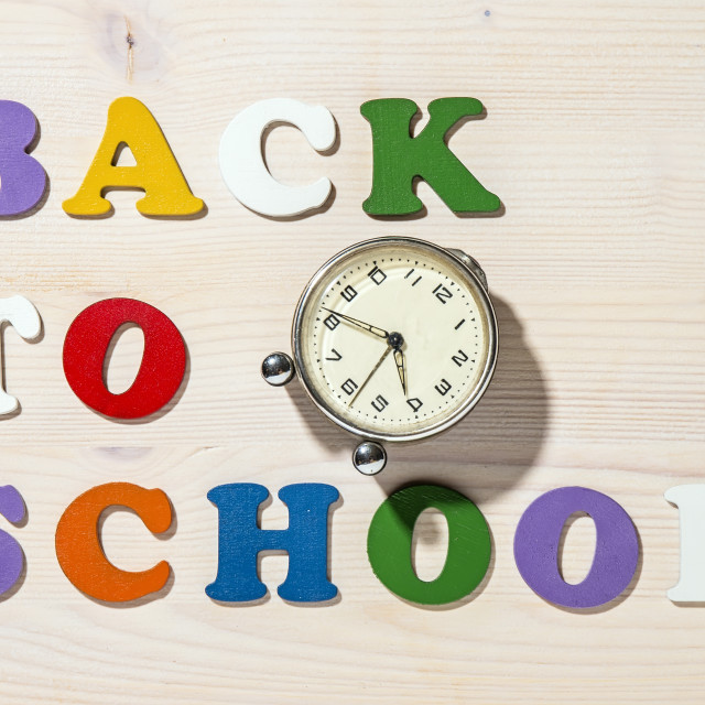 """Wooden Colorful Letters Spelling Back To School With Old Clock"" stock image"