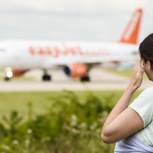 """""""Woman wiping her brow watching a plane depart"""" stock image"""