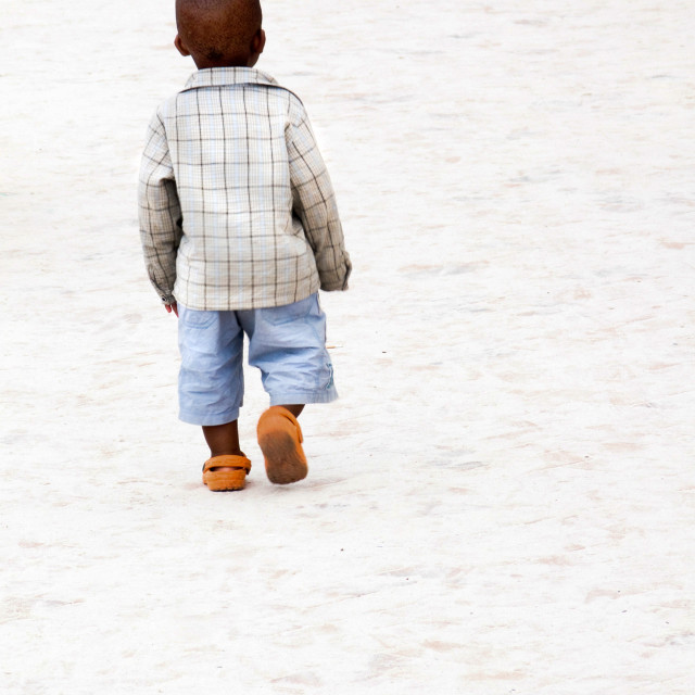 """A small (young) boy walking on the beach in his new orange shoes"" stock image"
