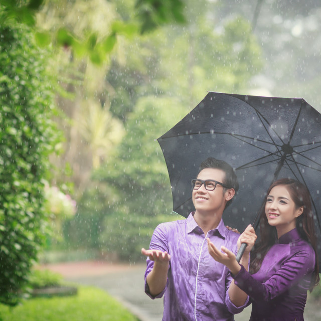 """Vietnamese couple with ao dai in the rain"" stock image"