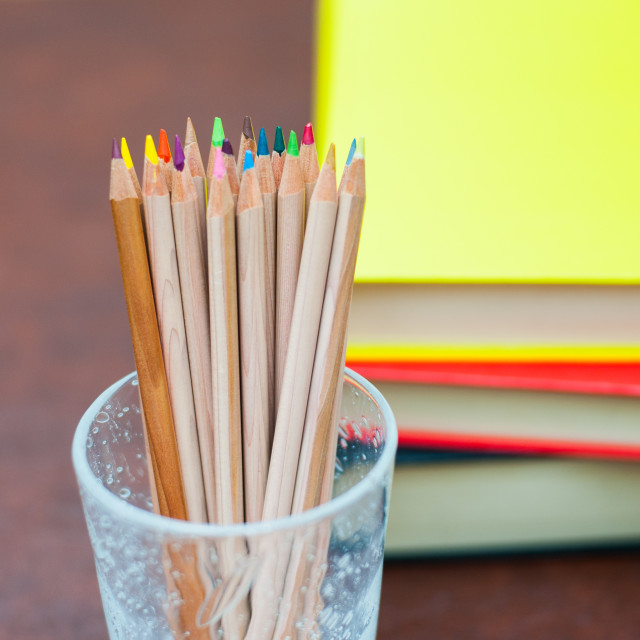 """""""Colored pencils with pile of books in background"""" stock image"""