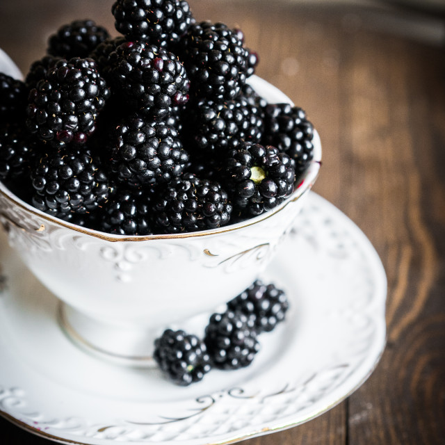 """Blackberries in a mug on wooden background"" stock image"