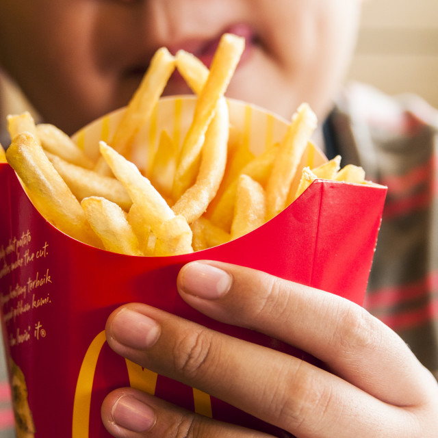"""""""Hungry Kid Holding French Fries"""" stock image"""