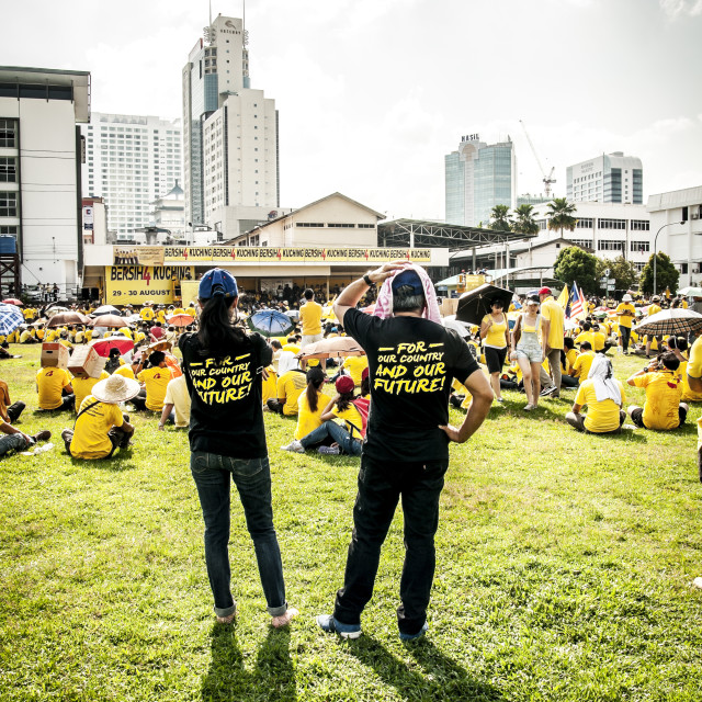 """Couple standing behind crowd of yellow shirt activists"" stock image"