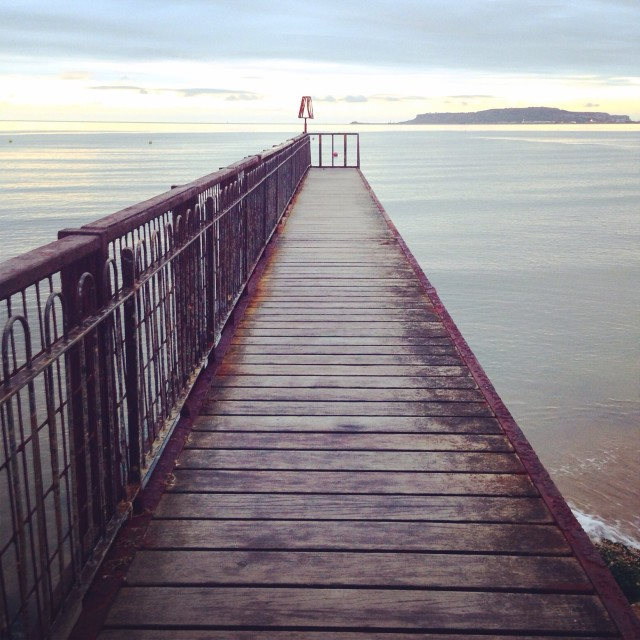 """""""Wooden pier extends out to sea"""" stock image"""