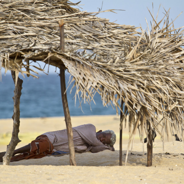 """Old man resting in shadow in Sri Lanka beach"" stock image"
