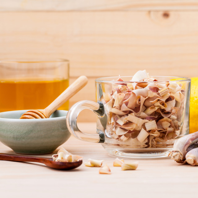 """Cup of herbal tea with dried lemon grass ,honey and lemon on wooden background."" stock image"