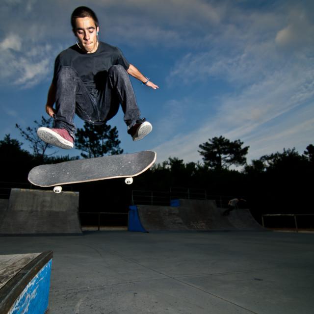 """Skateboarder on a flip trick"" stock image"