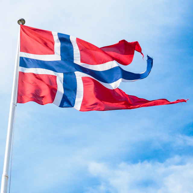 """The Royal flag of Norway on a pole towards blue and white sky in daylight"" stock image"