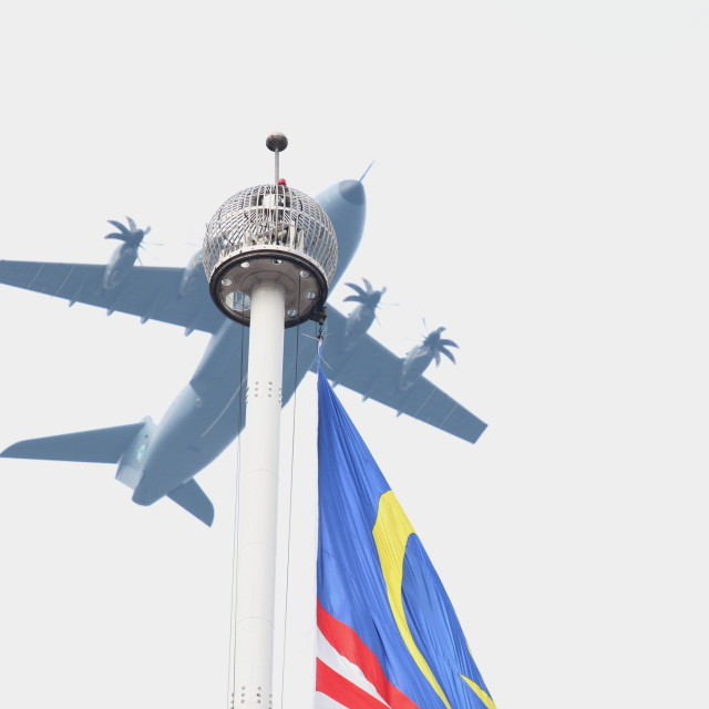 """""""Military aircraft flying over the Malaysian flag pole"""" stock image"""