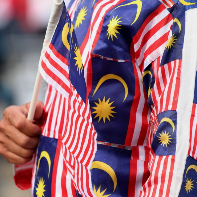"""man in malaysian flag jumpsuit holding a malaysian flag"" stock image"
