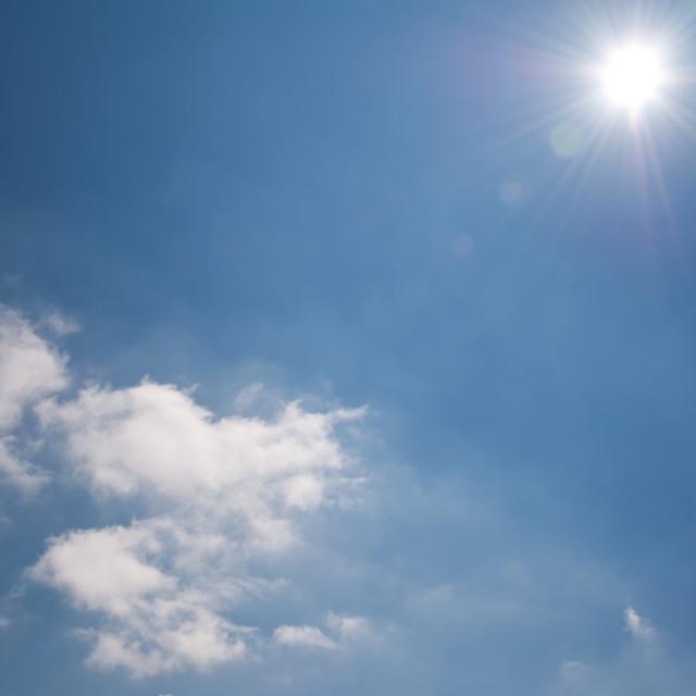 """Noon blue sky sunburst"" stock image"