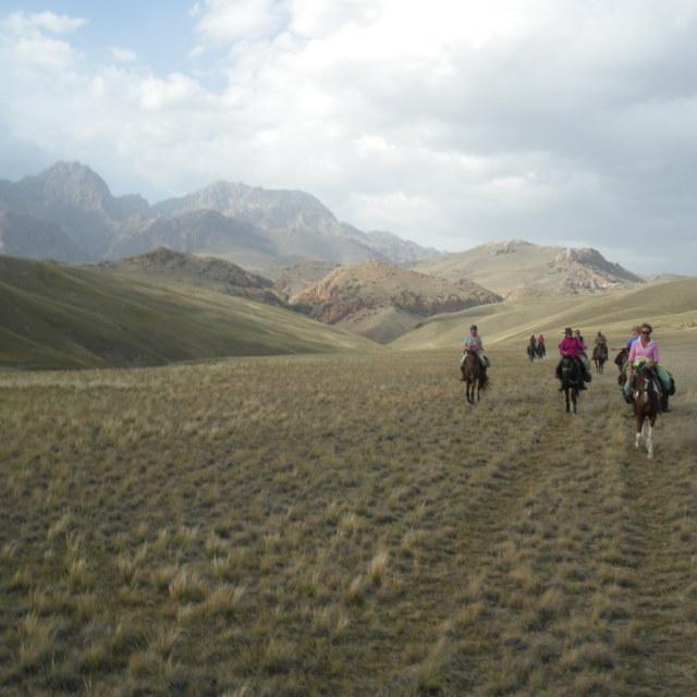 """Horseriding across plain, Kyrgyzstan"" stock image"