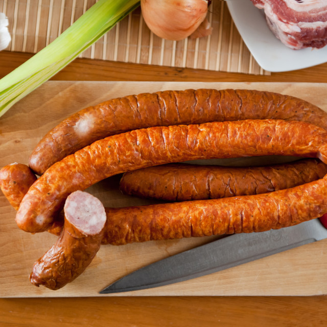 """Knife and smoked sausage on board"" stock image"