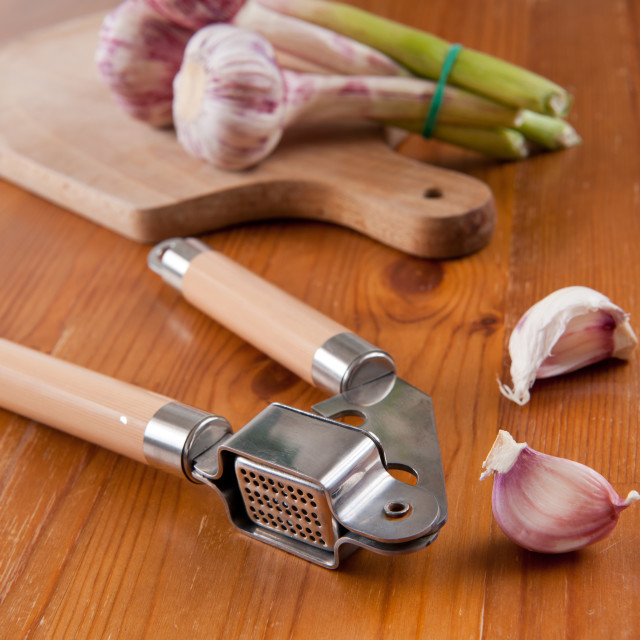 """Garlic press and cloves of garlic"" stock image"