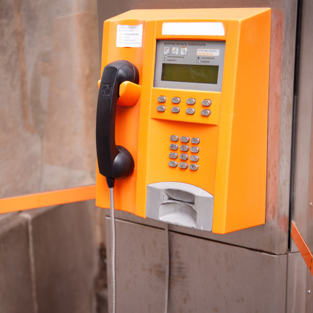 """Old orange telephone kiosk"" stock image"