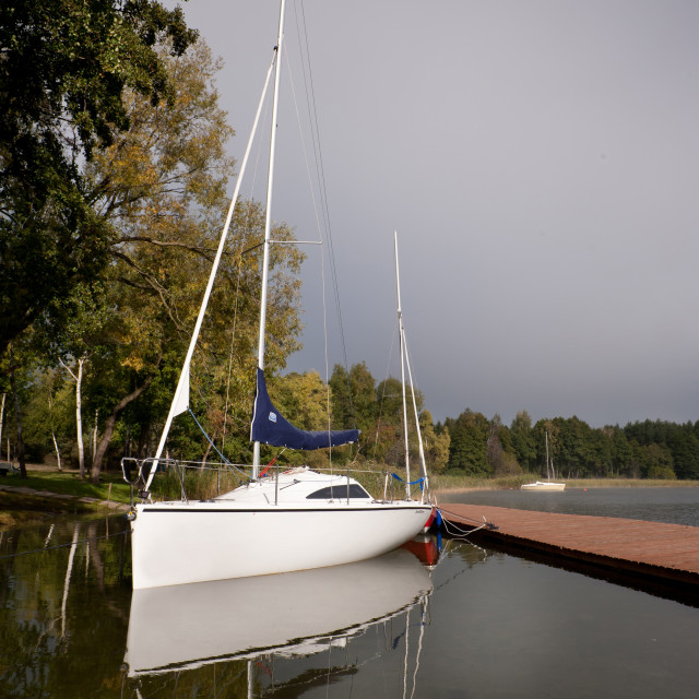 """Single white boat moored to boardwalk"" stock image"