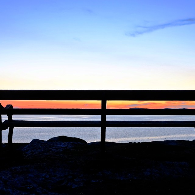 """""""The sun sets on a seaside seat"""" stock image"""