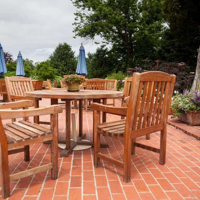 """Teak patio tables and chairs on brick deck"" stock image"