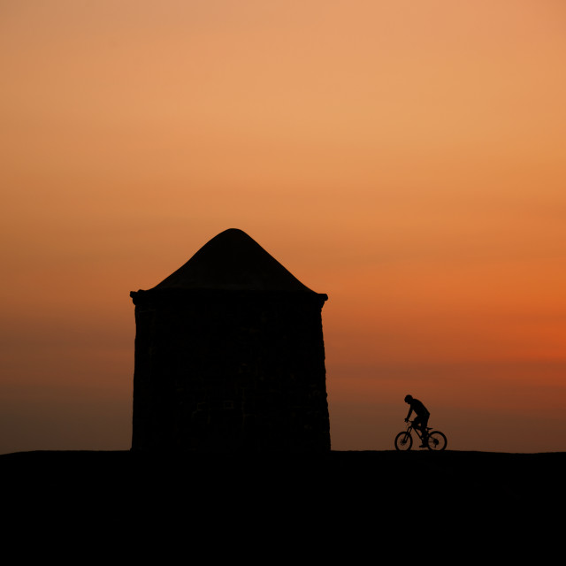 """""""A Silhouhette Cyclist At Sunset"""" stock image"""