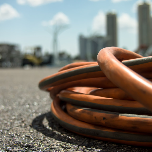 """The Orange Extension Cord on the Ground at the Constructionsite"" stock image"