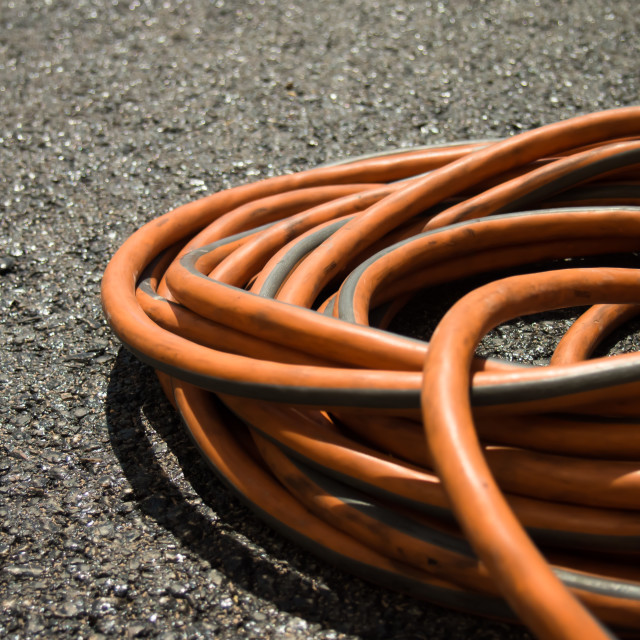 """""""The Orange Extension Cord on the Ground at the Constructionsite"""" stock image"""