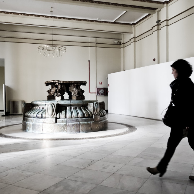 """Woman walking through exhibition room"" stock image"