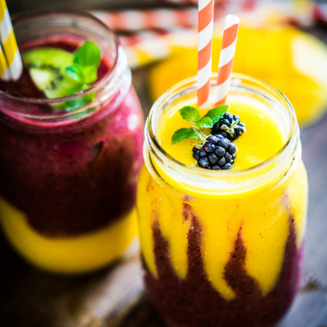 """Colorful two layer smoothies with mango and berries on rustic wooden background"" stock image"