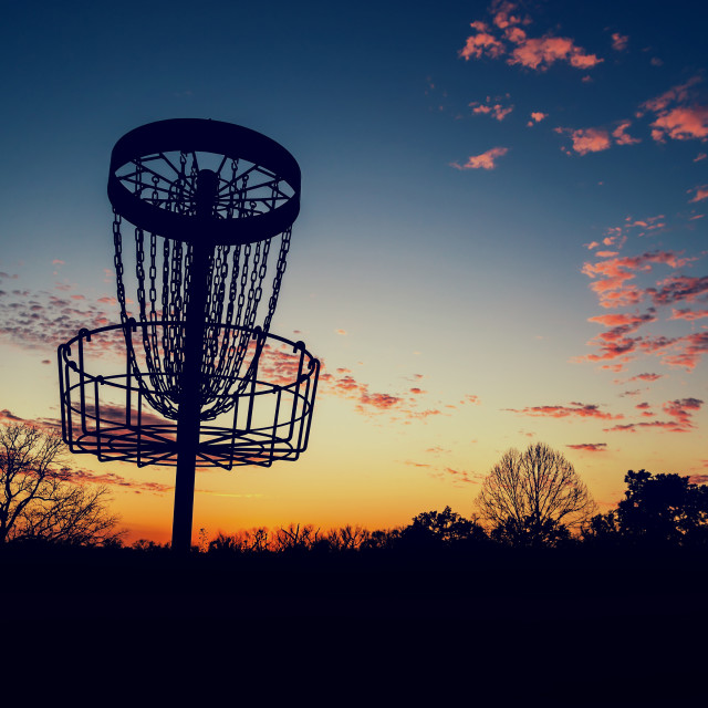 """Silhouette of disc golf basket against sunset"" stock image"