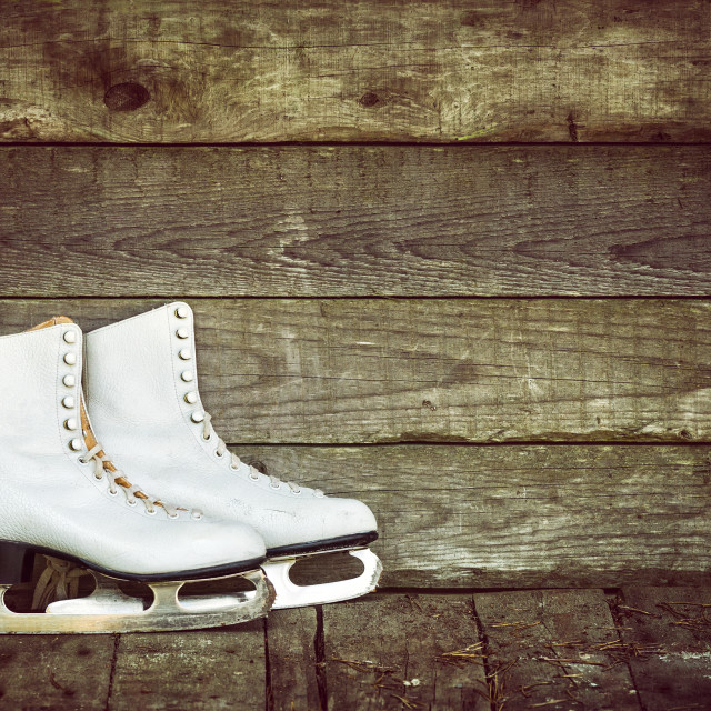 """Old ice skates against rustic background"" stock image"
