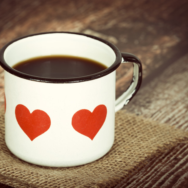 """""""Cup of coffee in an old enamel mug with hearts on vintage backgr"""" stock image"""