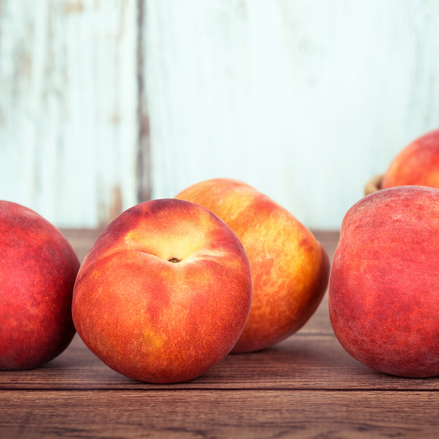 """Closeup of peach fruits on wooden table"" stock image"