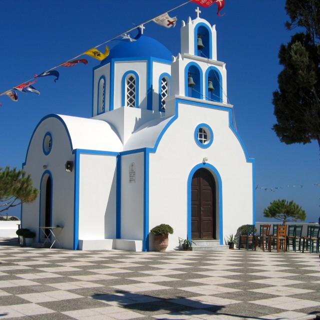 """Greece Santorini church chairs and tree"" stock image"