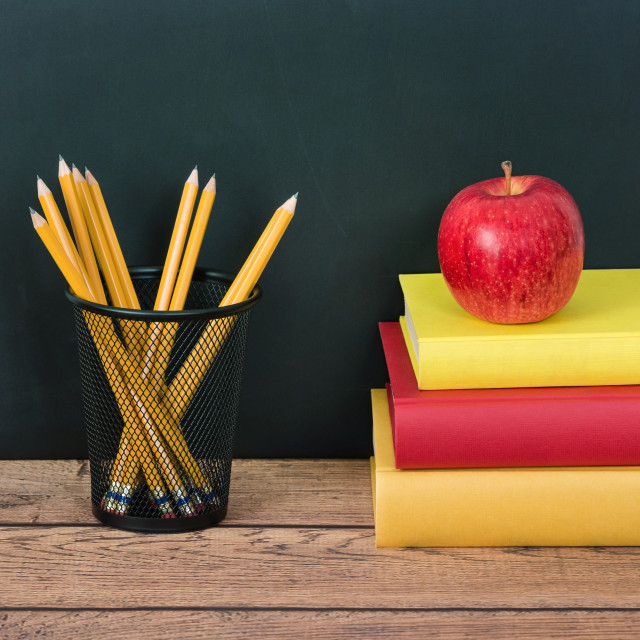 """Stack of school books with apple and pencils on the desk"" stock image"