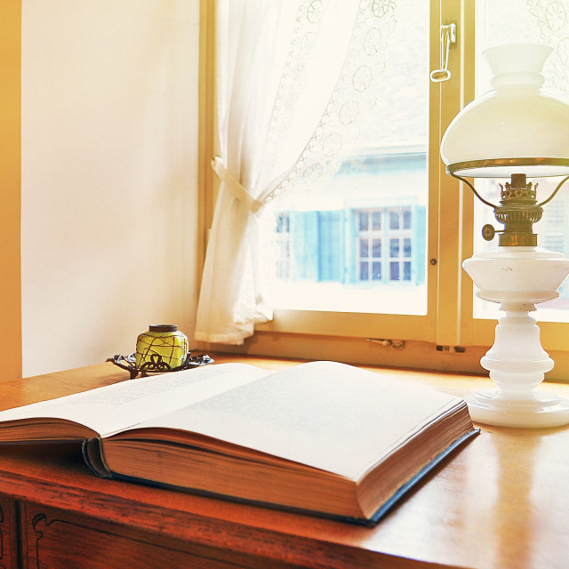 """""""Old petroleum-lamp and a book against window"""" stock image"""