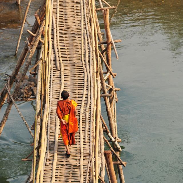 """A monk on a bamboo bridge"" stock image"