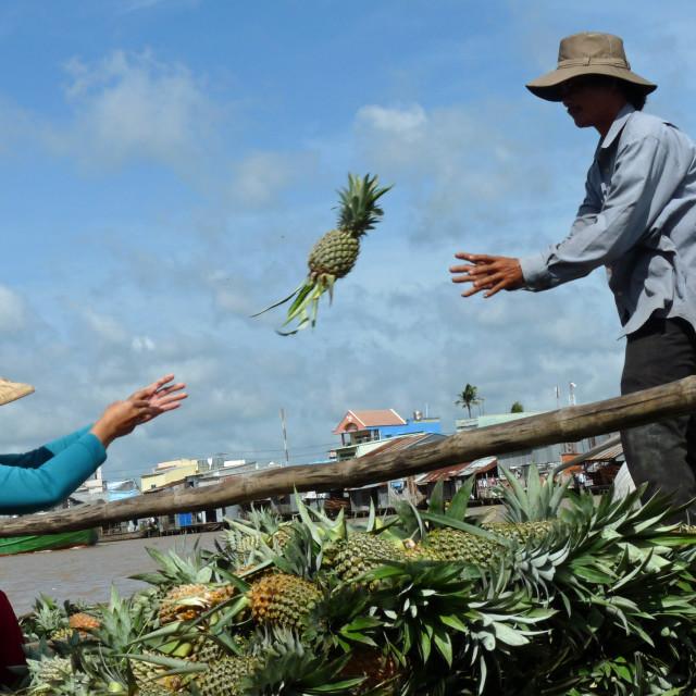 """""""Vietnamese woman throwing pineapple to man"""" stock image"""