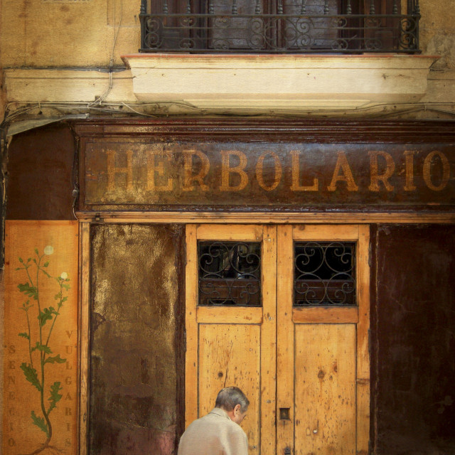 """Man entering store front Herbolario"" stock image"