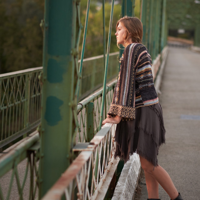 """Fashionable Teenage Girls Leaning Against the Rail of a Bridge."" stock image"