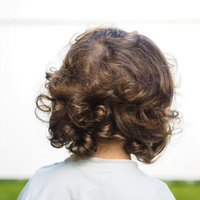 """Little caucasian person with curly hair staring at watching a white wall"" stock image"