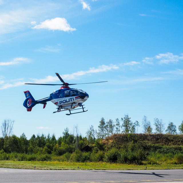 """Police helicopter from norwegian authorities hoovering over landing field"" stock image"
