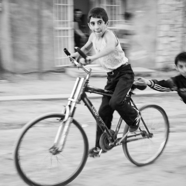 """Boys playing with a bicycle"" stock image"