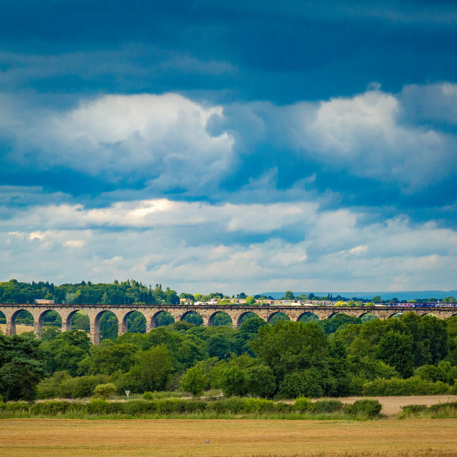 """Train crossing a viaduct under a brooding sky"" stock image"