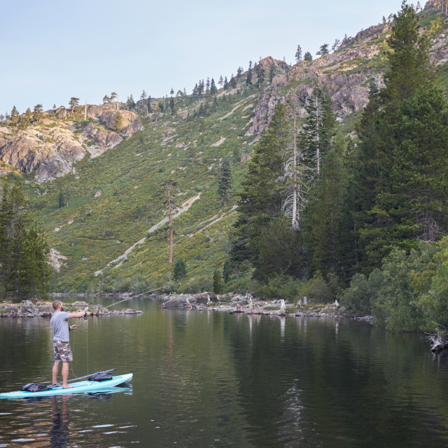 """""""A Young Man FIshing from a Paddle Board on a Mountain Lake."""" stock image"""